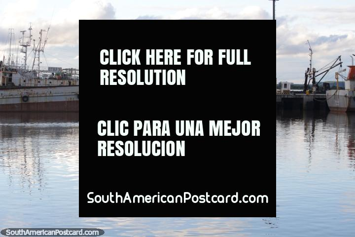 2 men row past boats moored at the port in Fray Bentos. (720x480px). Uruguay, South America.