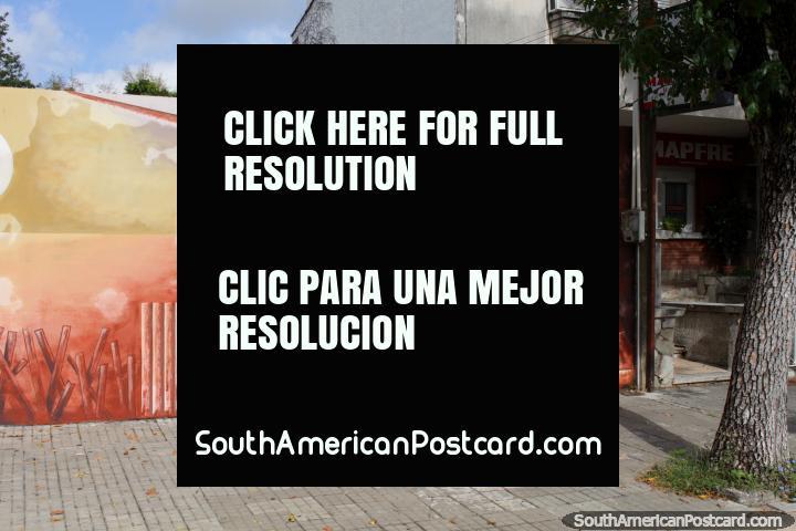 Mural que representa o trabalho duro nos portos com 2 porcos, amoladores e guindaste, Fray Bentos. (720x480px). Uruguai, América do Sul.