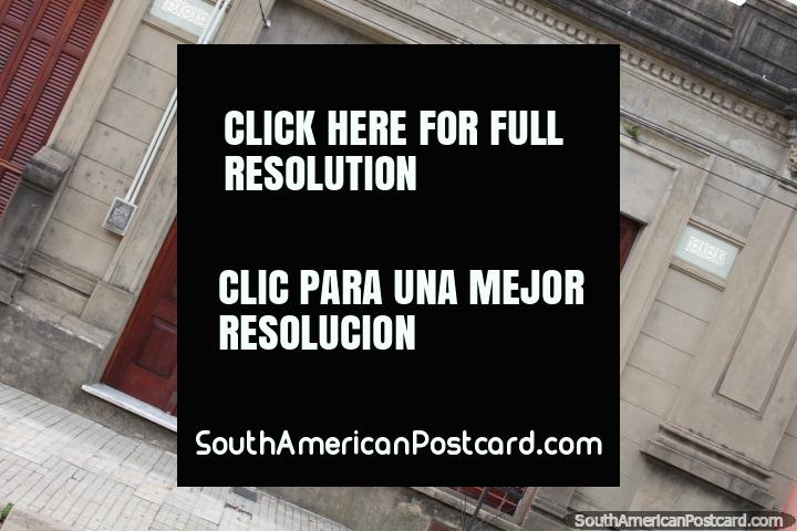 Un antiguo edificio con puerta de madera, ventanas y persianas en Fray Bentos. (720x480px). Uruguay, Sudamerica.
