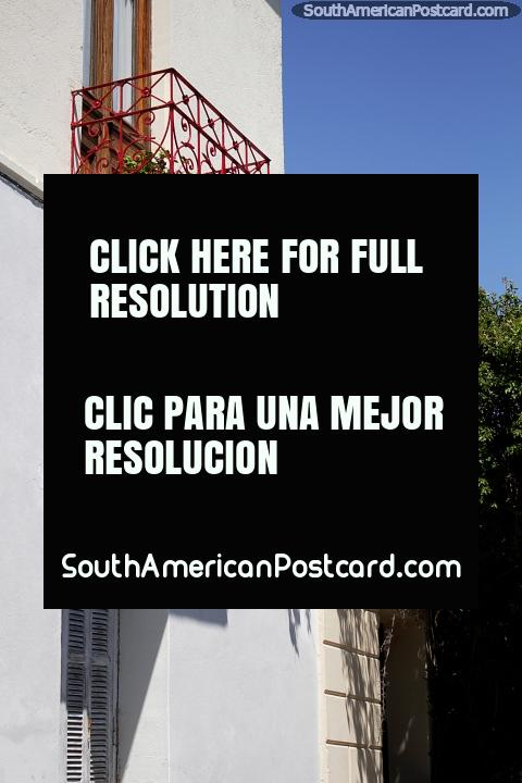 Balcão de ferro vermelho, uma fachada branca e flores vermelhas, as ruas em Colônia. (480x720px). Uruguai, América do Sul.