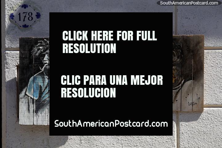 Rapaz em uma esquina de rua e homem com copos, pinturas em madeira em Colônia. (720x480px). Uruguai, América do Sul.