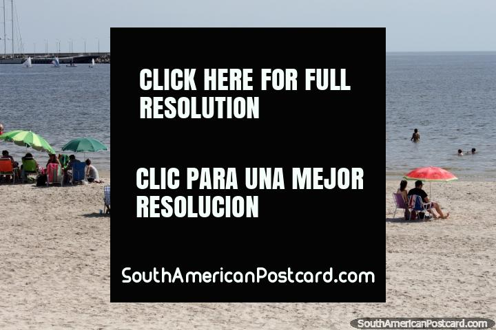 People enjoy the beach and waters in Piriapolis while people sail in the distance. (720x480px). Uruguay, South America.