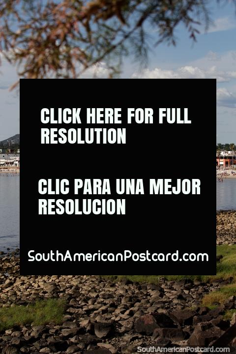 View across the rocks and still waters to the beach, city and mountain in Piriapolis. (480x720px). Uruguay, South America.