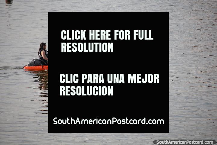a pair of girls paddle a kayak on the calm waters in Piriapolis, rent from Samoa Kayaks. (720x480px). Uruguay, South America.