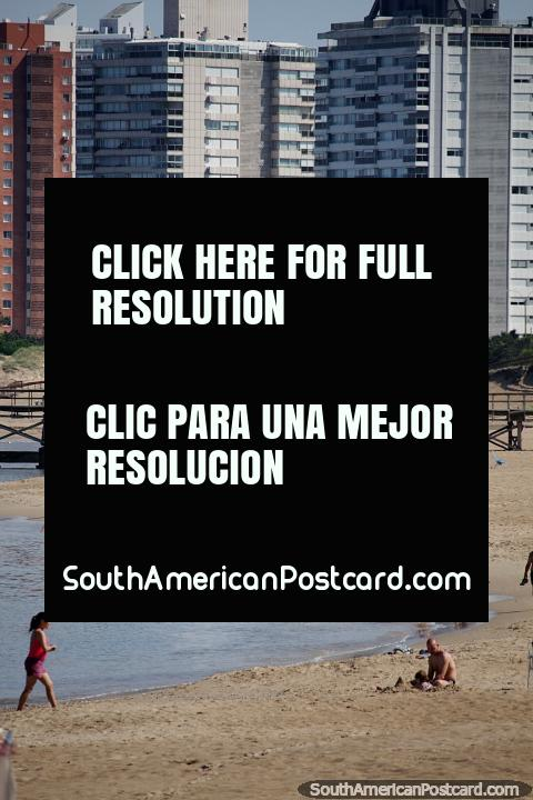 Mansa Beach, jetty and apartments, people walking in the morning in Punta del Este. (480x720px). Uruguay, South America.