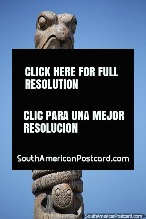 Head of an eagle and a small figure, a sculpted totem pole, wooden monument in Punta del Este. (480x720px). Uruguay, South America.