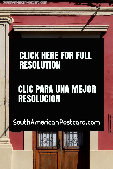 Wine and cream colored facade with a wooden door in Rocha, very stylish. (480x720px). Uruguay, South America.