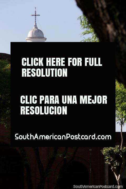 Igreja vermelha e de tijolo que se esconde atrás de árvores na praça pública em Treinta e Tres, a cúpula em cima. (480x720px). Uruguai, América do Sul.