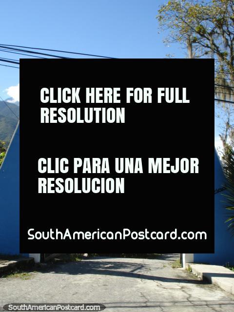 Vista a través de una puerta azul a propiedades en las colinas de Mérida. (480x640px). Venezuela, Sudamerica.