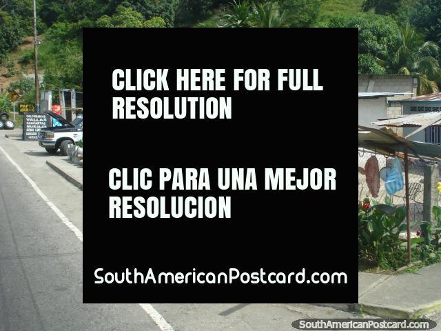 A man sells meat hanging from hooks on a street corner, Merida to Maracaibo. (640x480px). Venezuela, South America.