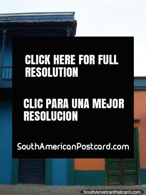 Edificio azul con balcón siguiente a construcción con una puerta de madera verde, Puerto Cabello. (480x640px). Venezuela, Sudamerica.
