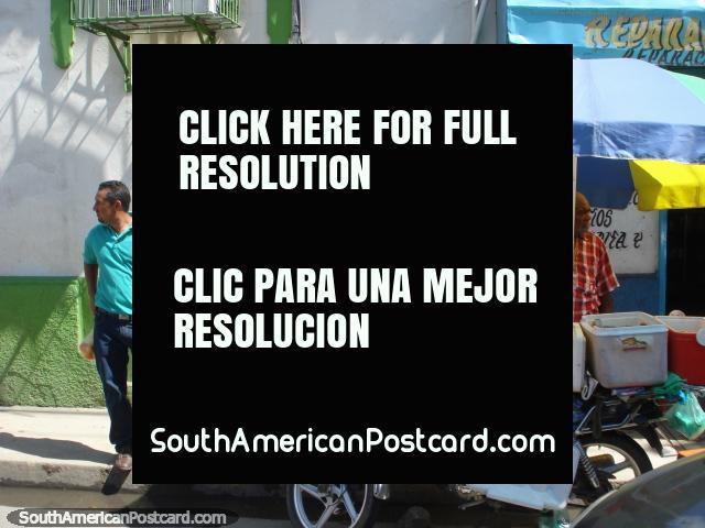 La gente en la calle en Porlamar, el hombre vende la comida de su motocicleta liviana. (640x480px). Venezuela, Sudamerica.