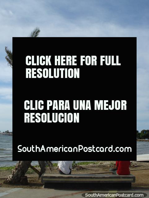 2 men sit on a bench under a palm tree in the morning at Boca de Rio on Isla Margarita. (480x640px). Venezuela, South America.