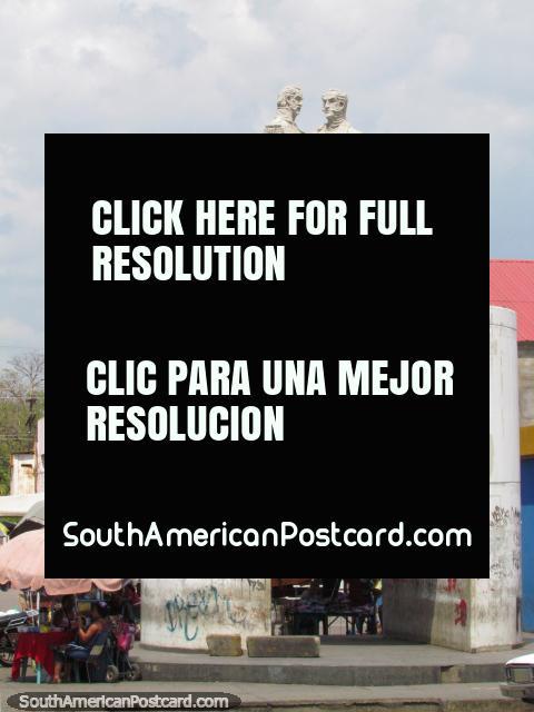 2 men shake hands Bolivar monument near the river in Barcelona. (480x640px). Venezuela, South America.