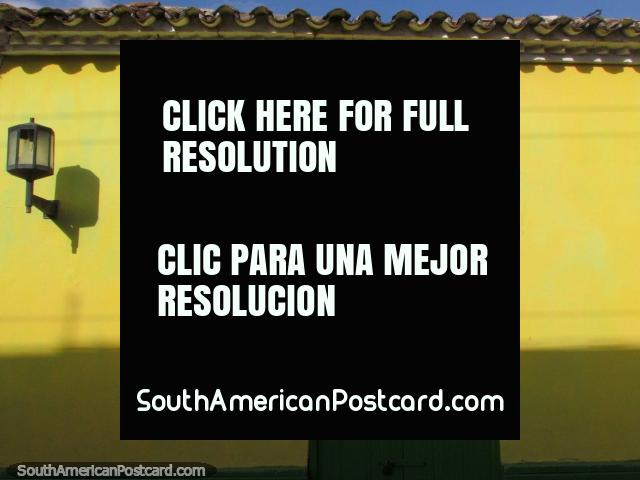 Porta de madeira verde e uma parede amarela com uma iluminação de rua em Coro. (640x480px). Venezuela, América do Sul.