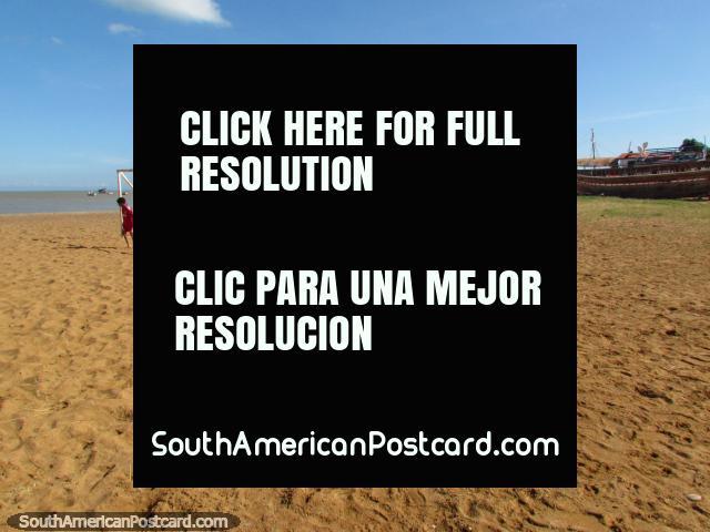 Boy stands in a goal on the sand at the beach in Coro - La Vela de Coro. (640x480px). Venezuela, South America.