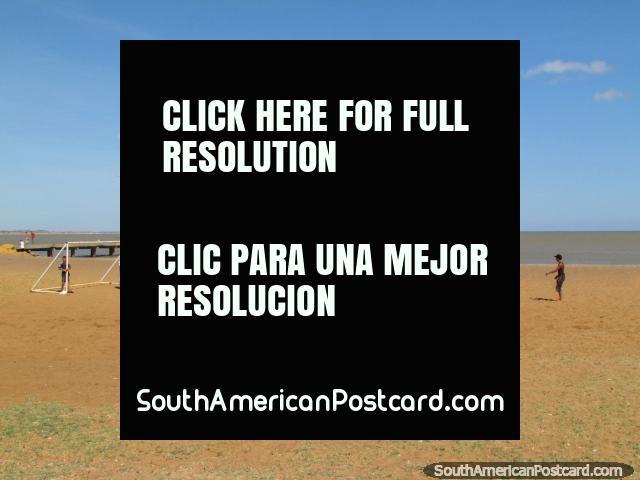 Os rapazes jogam o futebol na areia perto do cais em La Vela de Coro. (640x480px). Venezuela, América do Sul.