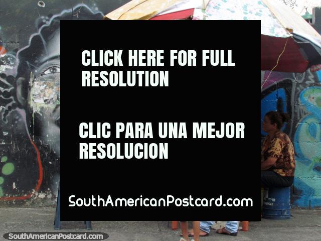 As meninas enfrentam a arte de grafite junto da senhora telefônica de Acarigua. (640x480px). Venezuela, América do Sul.