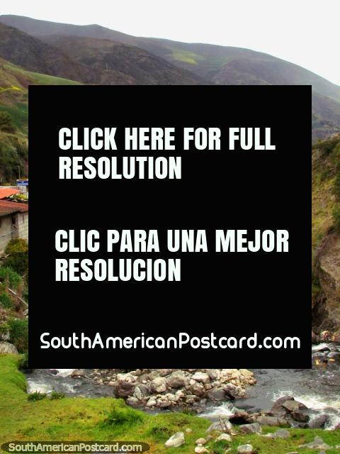 A horse eats grass on a river island above houses and mountains around Biguznos/Pedregal. (480x640px). Venezuela, South America.